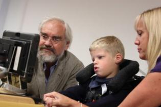 Company MD Paul Hawes, Matthew using eye gaze and Karen, his teacher.